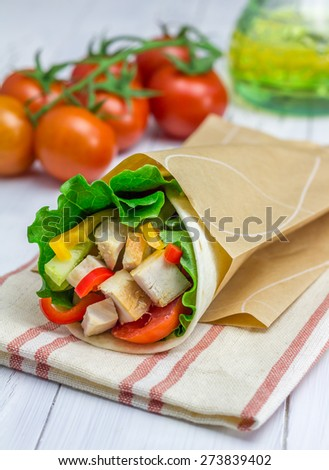 Tortilla wraps with roasted chicken fillet, fresh vegetables and sauce in paper bag