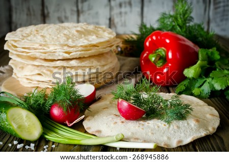 Tortilla wraps with vegetables. On the wooden table was a pile of pita. Vignette - stock photo