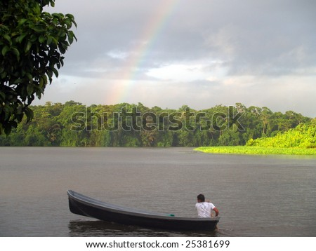 Tortuguero Rainbow - Looking south-west along  main channel from the public dock at Costa Rica's famos ecological preserve.   Note the rainbow .... it rains a lot here.  Taken October 2008 - stock photo