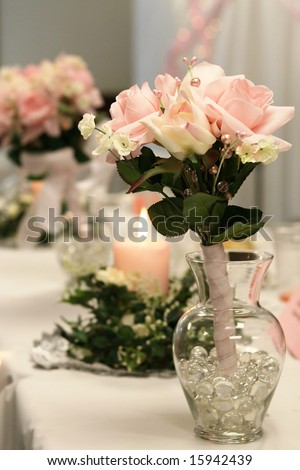 Toss bouquet in glass vase at a reception. - stock photo