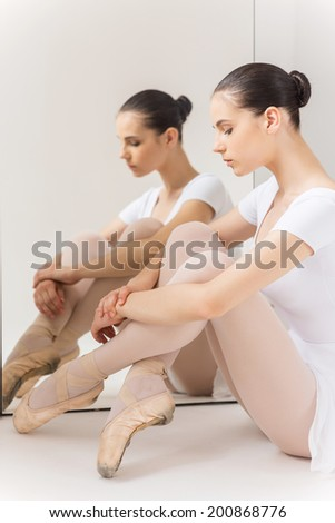 Total concentration. Beautiful young ballerina in white tutu sitting against a mirror  - stock photo