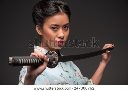 Total concentration. Side view portrait of young beautiful Japanese woman in kimono looking aggressively at camera and holding katana sword while standing against grey background - stock photo