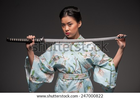 Total concentration. Young beautiful Japanese woman in kimono looking aggressively at camera and holding katana sword while standing against grey background - stock photo