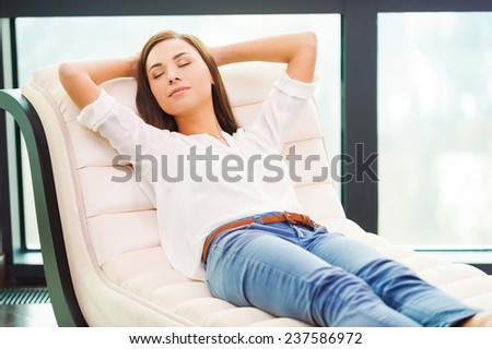 Total relaxation. Beautiful young woman holding hands behind head while sleeping on the couch  - stock photo