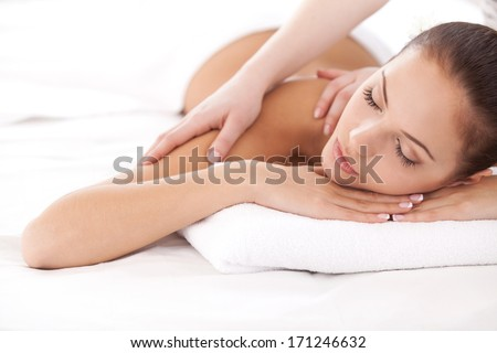 Total relaxation. Beautiful young woman lying on front and looking at camera while massage therapist massaging her shoulders - stock photo
