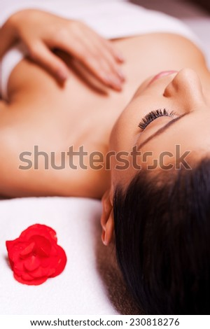 Total relaxation. Cropped image of beautiful young woman wrapped in towel lying on massage table and keeping eyes close - stock photo