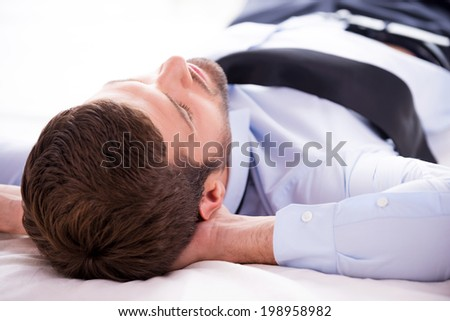 Total relaxation. Rear view of young man in shirt and tie holding hands behind head while sleeping in bed  - stock photo