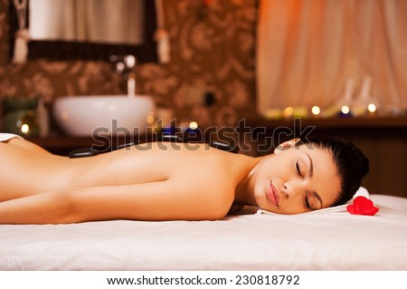 Total relaxation. Side view of beautiful young shirtless woman lying on massage table and keeping eyes closed with spa stones on her back - stock photo