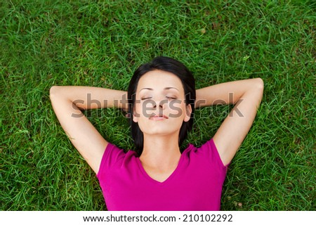 Total relaxation. Top view of beautiful young woman sleeping while holding hands behind head and lying on the green grass - stock photo