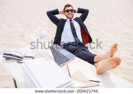 Total relaxation. Top view of relaxed young man in formalwear and sunglasses holding hands behind head and holding his feet on the table standing on sand - stock photo
