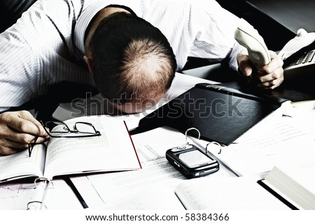 Totally desperate businessman with head on office desk top being overloaded with loads of work - stock photo
