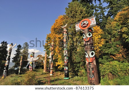 Totem in the park with fall foliage on the background - stock photo