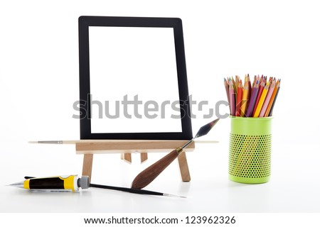 touch-pad supported by an easel, next to crayons, brushes and artist tools - stock photo