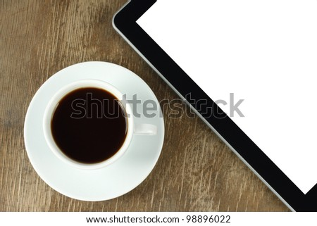 Touch screen device and cup of coffee on old wooden background - stock photo