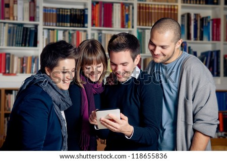 Touch screen tablet computer - group of students in library - stock photo