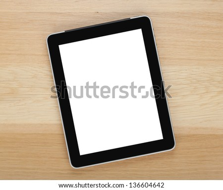 Touch screen tablet computer with blank screen on wooden table