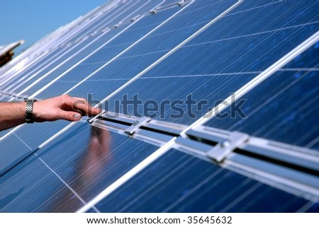 Touching a solar panel - stock photo