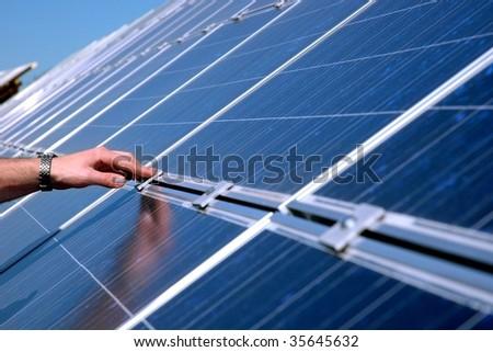 Touching a solar panel - stock photo