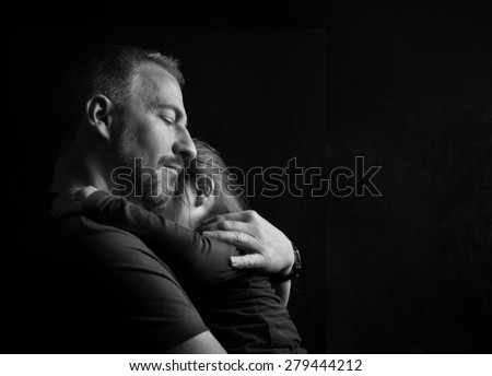 Touching Heart Felt Black and White Image of Father with Eyes Closed Hugging Young Daughter Tenderly with Dark Background with Copy Space - stock photo