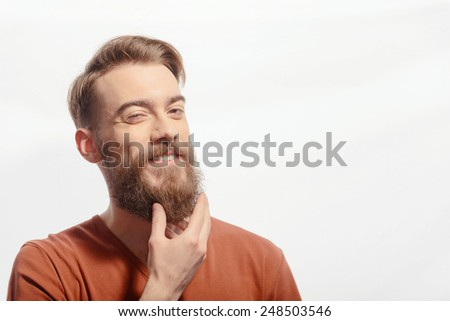 Touching his perfect beard. Closeup of young bearded man touching his beard while standing against white background