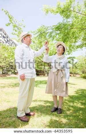 Touching the leaves of Japanese elderly couple - stock photo