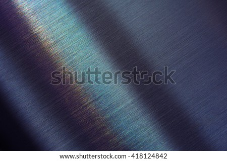 Tough brushed metal with slight rainbow like reflection. Shallow depth of field. - stock photo