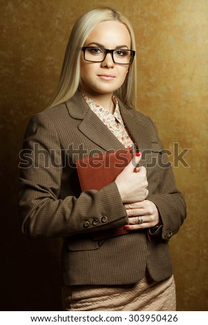 Tough business lady concept. Portrait of elegantly dressed young gorgeous blonde woman in trendy eyewear holding leather notebook. Smart casual style. Studio shot