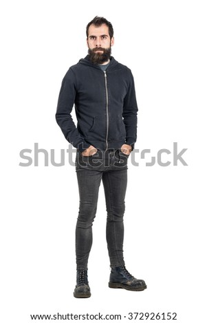 Tough confident stylish punker in black hooded sweatshirt looking at camera with hands in pockets. Full body length portrait isolated over white studio background.