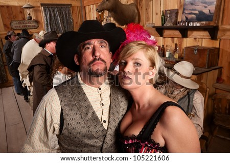 Tough couple in old American west bar setting - stock photo