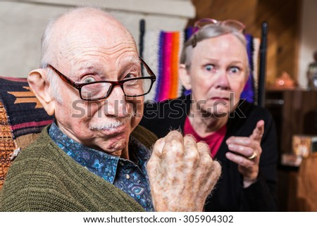 Tough elderly couple indoors with aggressive gesturing - stock photo