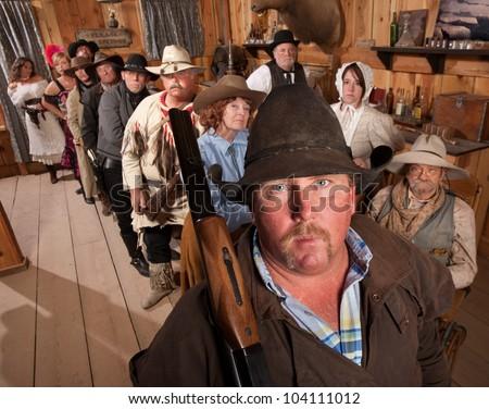 Tough gunfighter with shot gun over shoulder in old west bar - stock photo