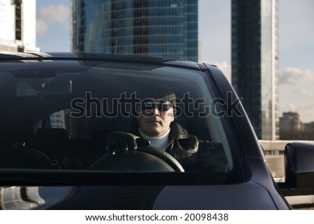 Tough guy in leather jacket in his car and skyscrapers at background
