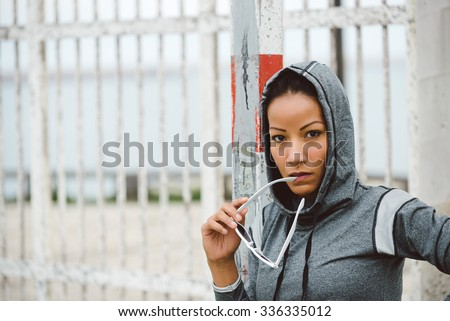 Tough looking fitness woman portrait. Sporty urban ethnic athlete wearing sunglasses and hood for outdoor workout.