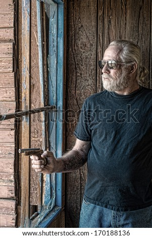 Tough looking old man in an old cabin next to a broken window pointing a vintage pistol - stock photo