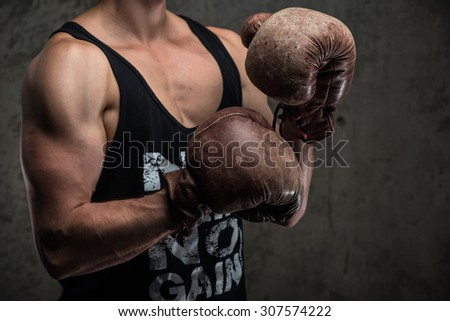 Tough male in vintage boxing gloves - stock photo