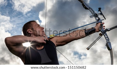 Tough man with bow and arrows, close up with cloudy sky at background - stock photo