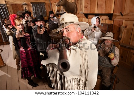 Tough old west desperado and group point their weapons in a bar - stock photo