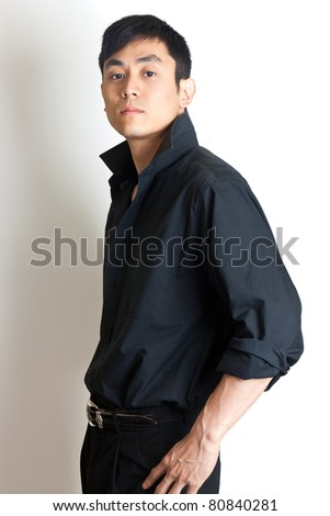 Tough young Asian man in black - stock photo