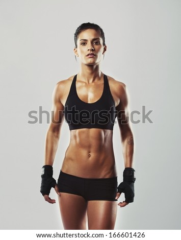Tough young woman standing on grey background. Muscular female looking at camera. Female bodybuilder wearing gloves ready for gym exercise. - stock photo