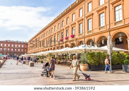 TOULOUSE, FRANCE - AUGUST 17, 2013: Tourists walking in the Le Capitole square. With 2 hectares, the area includes the city hall and a famous opera house.