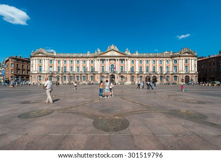 TOULOUSE, FRANCE - JUNE 02 2015: Capitole 135 meters long facade built in 1750 of the characteristic pink brick in Neoclassical style in Toulouse, Haute-Garonne, Midi Pyrenees, southern France. - stock photo