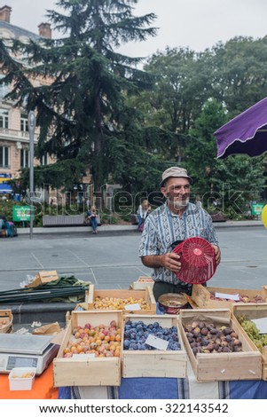 TOULOUSE, FRANCE - 12 SEPTEMBER 2015: Fruits market in Toulouse and unidentified man - stock photo
