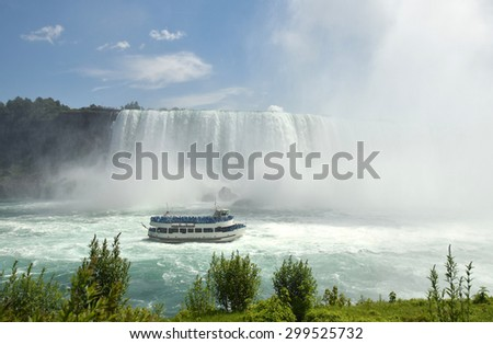 Tour boat near the base of Niagara Falls - stock photo