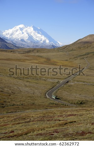 Tour bus on the road in Denali National Park - stock photo