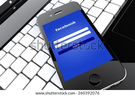 Tourin, Italy - March 14, 2015: Black Smart Phone with Facebook Social Network Screen on a laptop. - stock photo