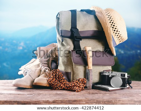 Tourism concept. Backpack, pair of boots and camera on blurred mountains background - stock photo