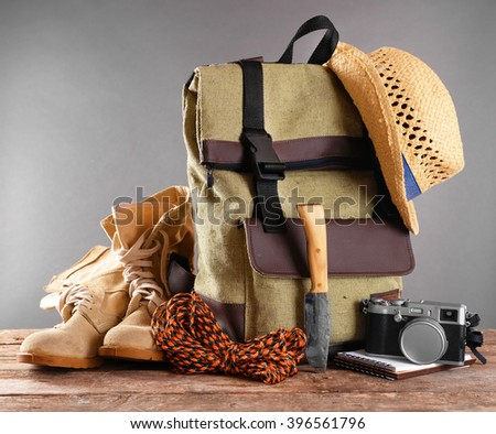 Tourism concept. Backpack, pair of boots and camera on wooden table against grey background - stock photo
