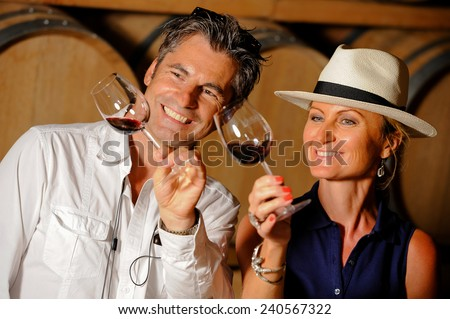 Tourism - Couple tasting wine in a cellar - stock photo