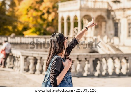 Tourism, girl show something by her hand - stock photo