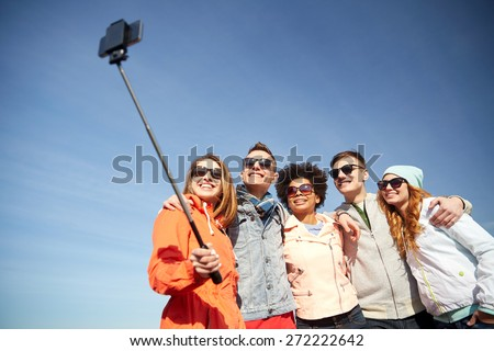 tourism, travel, people, leisure and technology concept - group of smiling teenage friends taking selfie with smartphone and monopod outdoors - stock photo